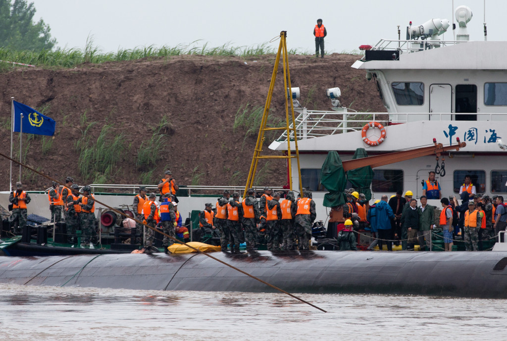 Chinese soldiers stand near a wrapped body as rescuers work on the capsized ship  on the Yangtze River. Hopes dimmed Wednesday for rescuing more than 400 people still trapped in the river cruise ship that overturned in stormy weather. The Associated Press