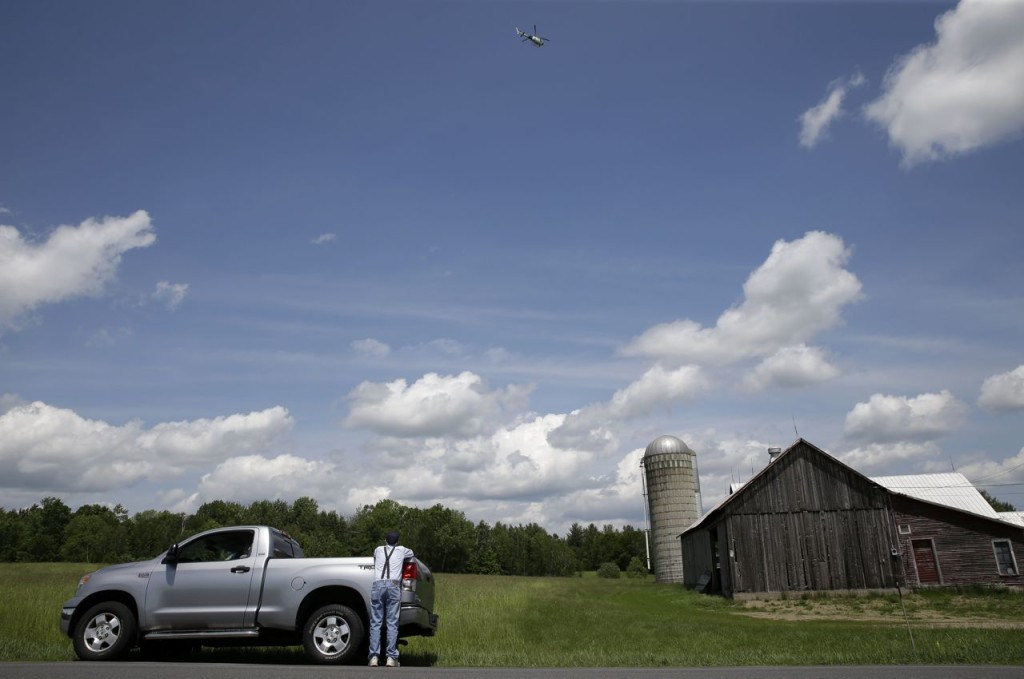 A man watches from the roadside as a law enforcement helicopter hovers over a wooded area near Dannemora, N.Y., Wednesday. The Associated Press