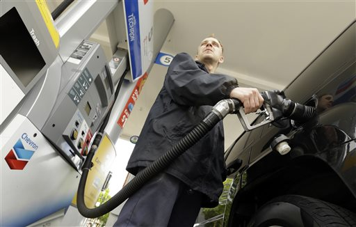 Attendant James Lewis pumps gas at a station in Portland, Ore. Even after the typical springtime run-up, the average price for gallon of regular gasoline should top out around $2.60, experts say. The Associated Press