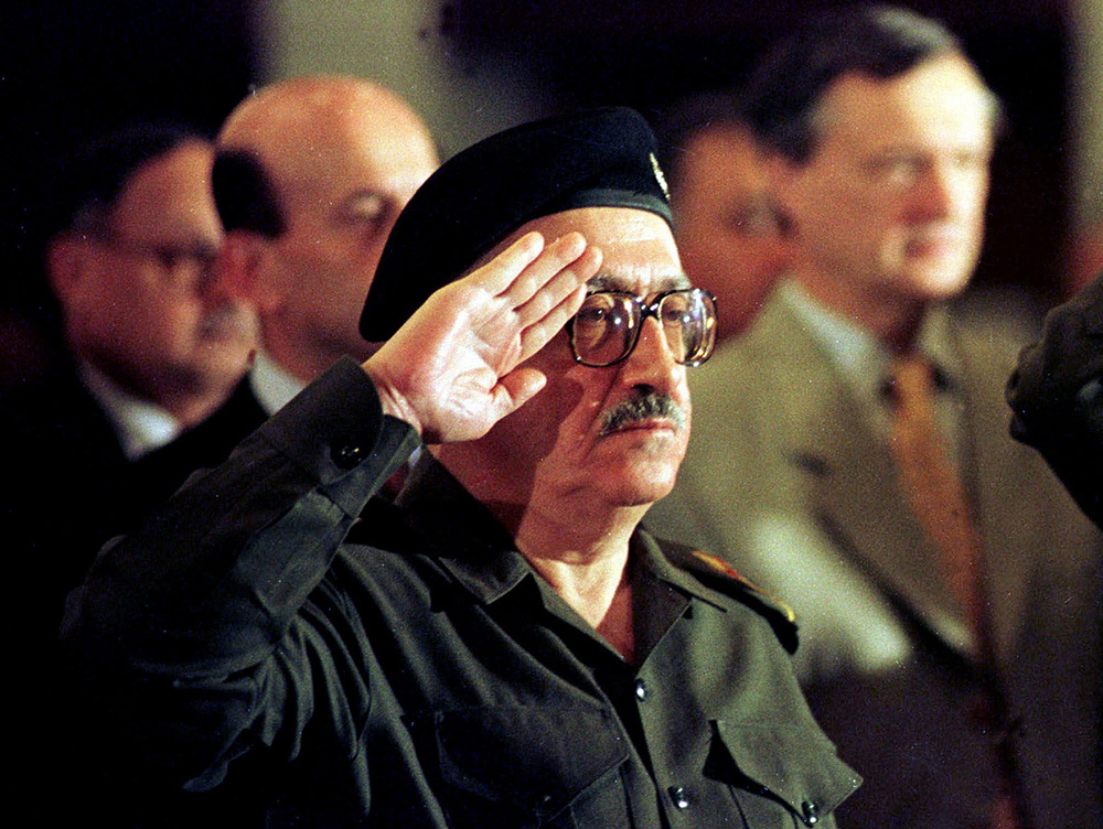 Then-Iraqi foreign minister Tariq Aziz stands at attention as the Iraqi national anthem is played at a conference in Baghdad in this 1998 photo, The Associated Press
