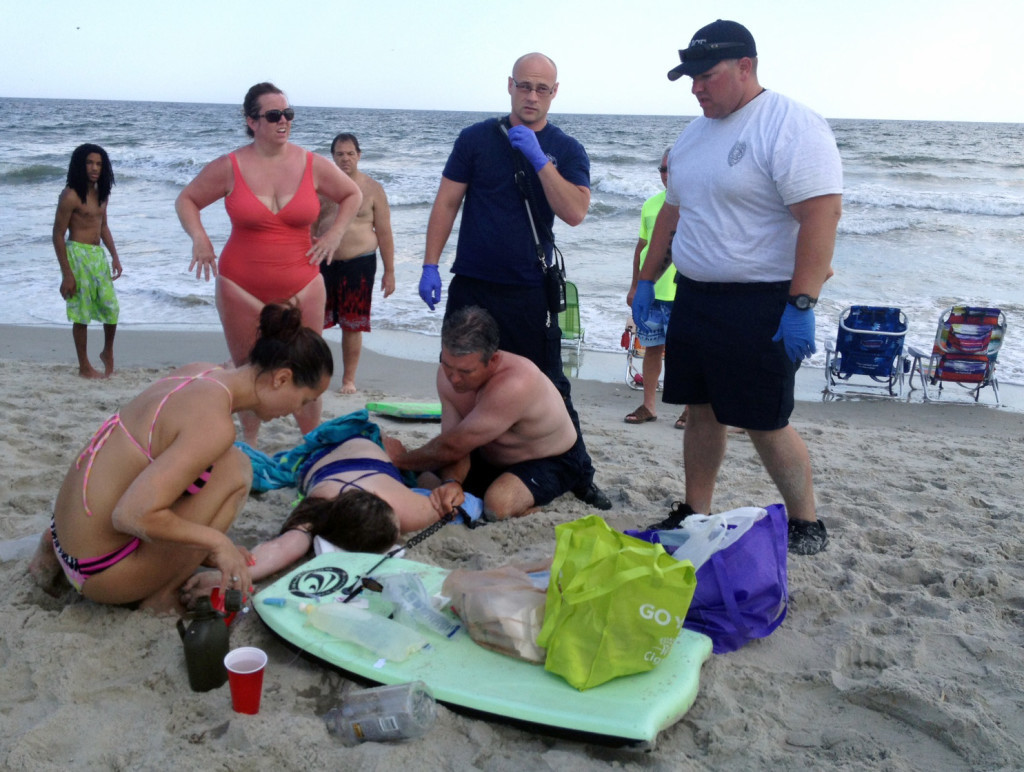 People assist a teenage girl at the scene of a shark attack in Oak Island, N.C., Sunday, June 14, 2015. Mayor Betty Wallace of Oak Island, a seaside town bordered to the south by the Atlantic Ocean, said that hours after the teenage girl suffered severe injuries in a shark attack Sunday a teenage boy was also severely injured.