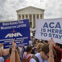 Supporters of the Affordable Care Act hold up signs as the opinion for health care is reported outside of the Supreme Court Thursday. An additional major opinion on gay marriage remains to be released before the term ends at the end of June. The Associated Press