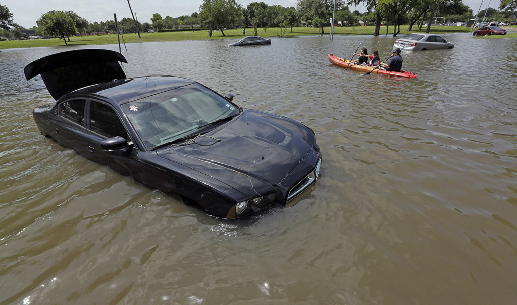 A boat paddles down a flooded street in Houston in this May 26, 2015, photo. A NOAA climate scientist calculates that cmore than 200 trillion gallons of water fell on the contiguous U.S. in May. The Associated Press