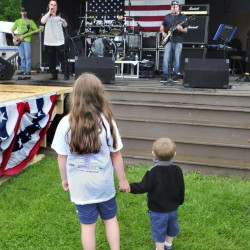 Taylor Denis, left, and Blake Whitman watch Right Amount of Wrong perform Wednesday at Fort Halifax Park in Winslow on the opening day of the Winslow Family 4th of July.