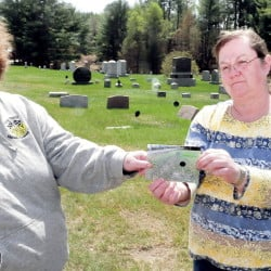 Penny Picard-Sampson, left, a member of the Board of Unity selectmen and cemetary committee and committee member Lynn Warman hold a photograph of a Pond Cemetery grave covered with gravel and dust from nearby Kanokolus Road. Selectmen Tuesday night agreed to have a half-mile stretch of road that goes by the cemetery paved.