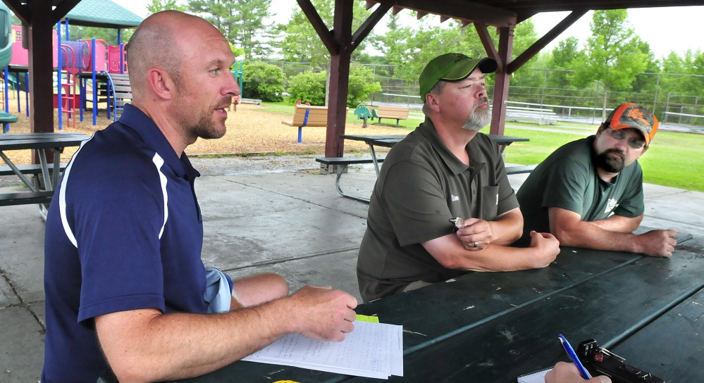 Waterville Parks and Recreation Director Matt Skehan, left, and employees Steve Buzzell and Sam Green discuss the department's carry-in-and-carry-out policy at city parks, including the North Street park in Waterville on Wednesday. There are no longer any trash cans at the park. Those who use the park are expected to remove their own trash.