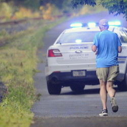A jogger approaches a Gardiner police cruiser blocking the Kennebec River Rail Trail in Farmingdale on Friday morning. A body was discovered on the tracks behind the Farmingdale Town Office at dawn, according to State Police, who are investigating the death as a suicide.