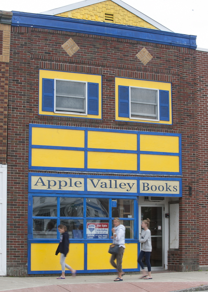 Pedestrians walk past the now-closed Apple Valley Books on Monday in Winthrop.