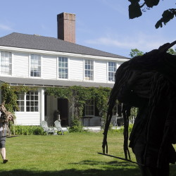 "Arielle Cousens, left, and Benjamin Stoodley carry the two pieces of their sculpture ""Navi"" onto the lawn of the Vaughan Homestead on Friday in Hallowell. The Augusta artists installed the driftwood and welded sculpture ahead of a reception for several pieces on display at the homestead, a nonprofit arts and cultural institution."