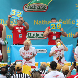 "Competitors, including Miki Sudo, second from left, and Sonya ""Black Widow""  Thomas, second from right, take part in Nathan's Famous Fourth of July International Hot Dog Eating Contest women's competition Saturday in the Coney Island section in the Brooklyn borough of New York."