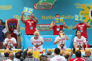 """Competitors, including Miki Sudo, second from left, and Sonya """"Black Widow""""  Thomas, second from right, take part in Nathan's Famous Fourth of July International Hot Dog Eating Contest women's competition Saturday in the Coney Island section in the Brooklyn borough of New York."""