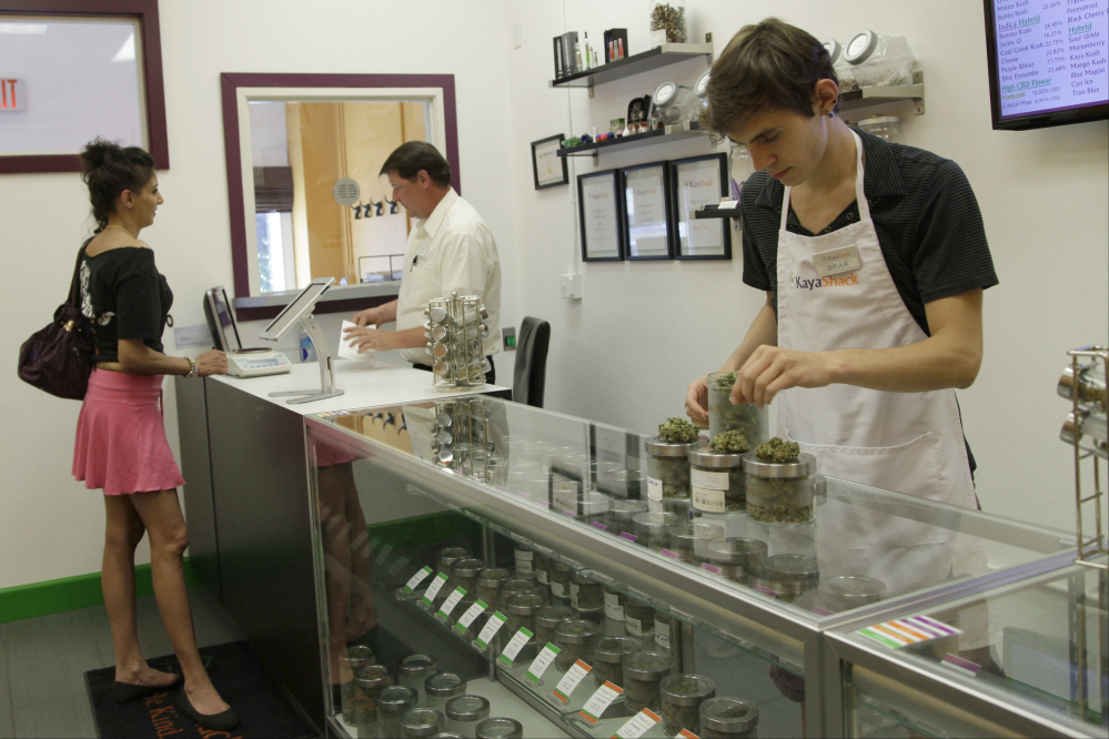 In this Friday, June 26, 2015 file photo, employees at the medical marijuana dispensary Kaya Shack help a customer choose her products, in Portland, Ore.