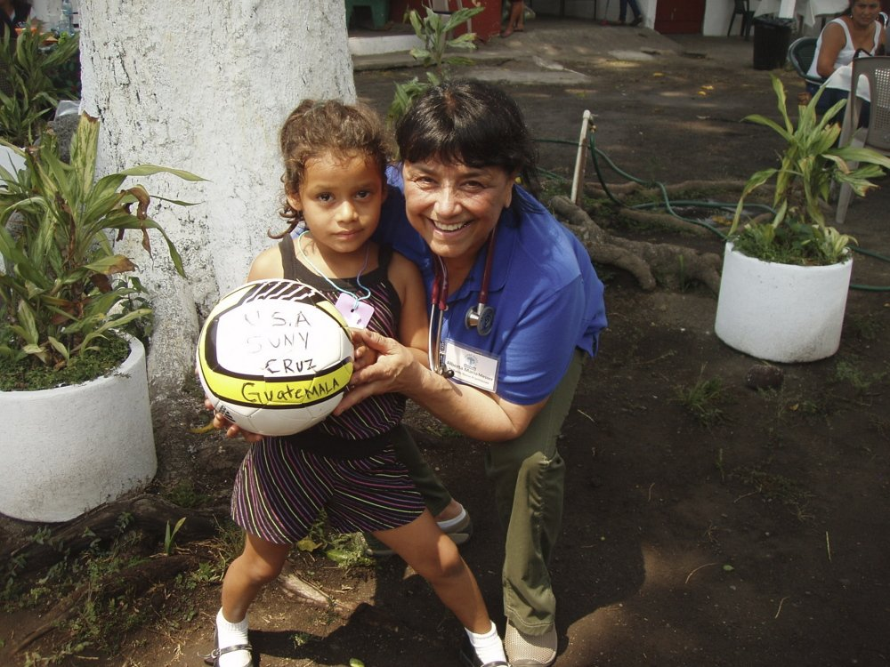 Alberta Longone-Messer, a pediatric nurse practitioner from Wayne, shares a moment with a child from the Escuintla region of Guatemala. Longone-Messer is leading an effort to provide clean water to thousands of people in the area.