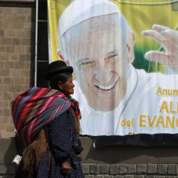 "An Aymara indigenous woman walks past a billboard featuring Pope Francis with a message that reads in Spanish: ""Announcing the joy of the Gospel"" in La Paz, Bolivia, Friday."