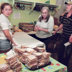 Volunteer Meg Nadeau, a member of the Winslow High School Honor Society, assists Linda Provencher and John Roy with food they selected at the Evening Sandwich Program held daily at the Universalist Unitarian Church in Waterville recently.