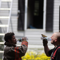 Litchfield firefighter Zakk McKinney, right, and Captain Michael Sherman cool off Sunday after helping extinguish a blaze inside a home off Route 126 in Litchfield.