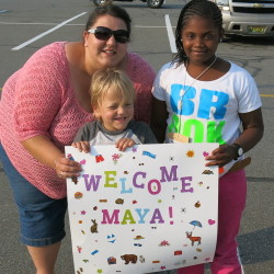 Megan Cyr, of Brooks, and her son Aidin welcome Maya on Monday as 20 children from New York City arrived for the annual Fresh Air Fund visit to central Maine.