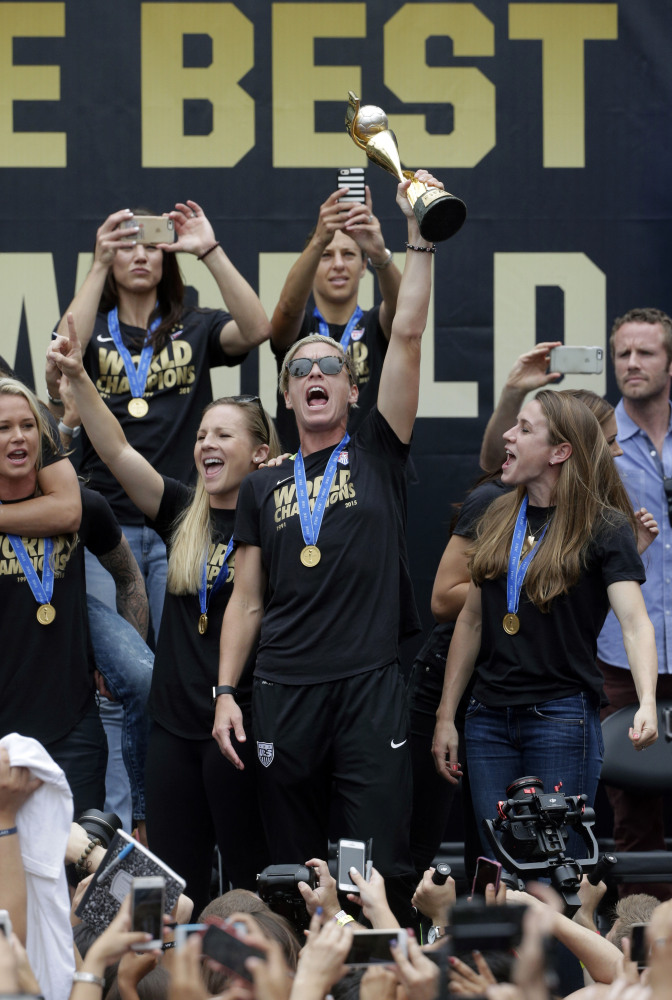 U.S. women's soccer team forward Abby Wambach, center, hoists the trophy while celebrating the team's World Cup championship during a public rally Tuesday in Los Angeles. This was the first U.S. stop for the team since beating Japan in the Women's World Cup final Sunday in Canada.
