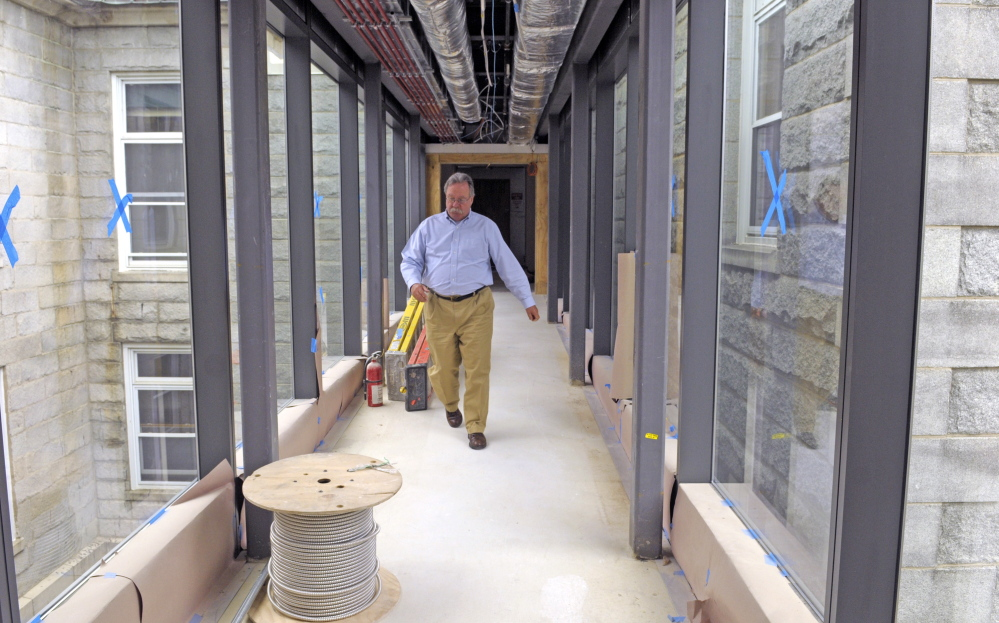 Kennebec County Administrator Robert Devlin walks through a new glassed-in walkway inside the courtyard of the old Kennebec County Courthouse in Augusta on Thursday.