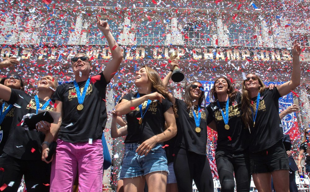 In a flurry of confetti, Abby Wambach, third from left, gestures to the crowd, surrounded by her teammates during a celebration for the U.S. Women's World Cup soccer champions at New York's City Hall, following their ticker tape parade up Broadway's Canyon of Heroes on Friday.