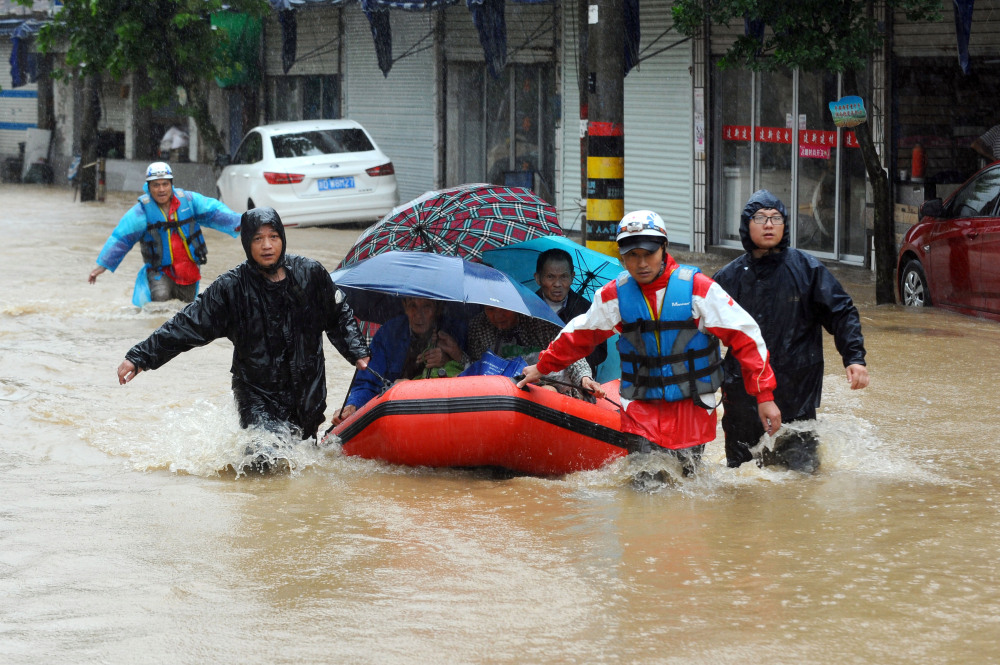 Rescuers use an inflatable boat to evacuate residents from a neighborhood flooded by heavy rains from Typhoon Chan-Hom in Shaoxing in eastern China's Zhejiang province on Saturday. Some 1.1 million people were evacuated from coastal areas of Zhejiang and more than 46,000 in neighboring Jiangsu province ahead of the storm.