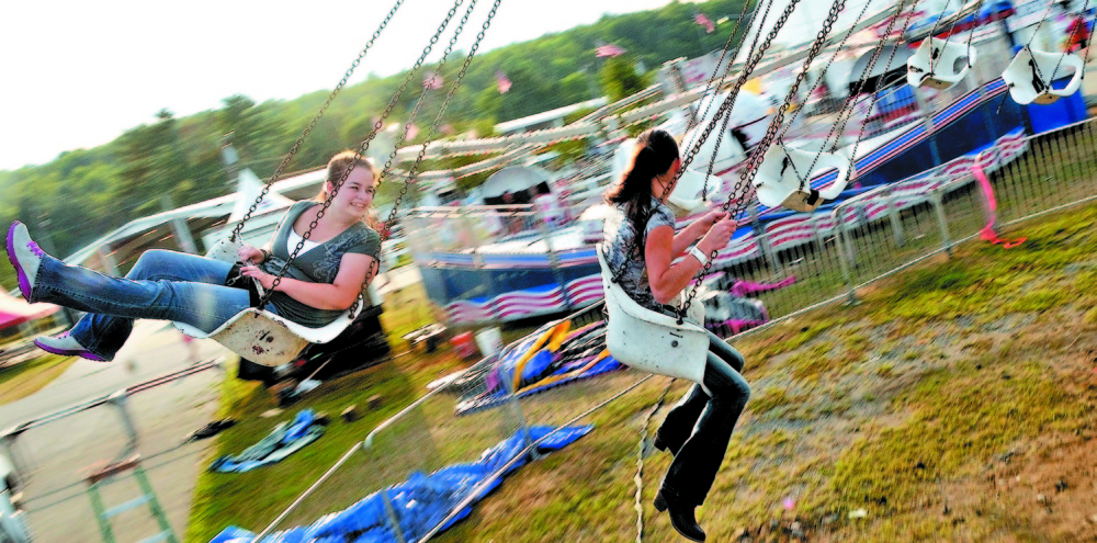 Krista Rogers, 19, left, and Megan Miville, 19, both of Fairfield, spin around on the Trapeze Swings in 2014 at the Skowhegan State Fair.