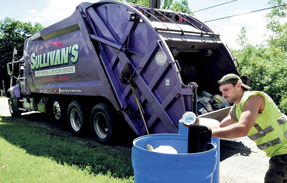 """Jerry Allen, an employee of Sullivan's Waste, empties recyclables into a company truck recently. The Thorndike company has the contract to pick up Waterville's residential recycling the first and third weeks of the month. Mayor Nick Isgro and city councilors were surprised that the city administration announced that no arrangements were to be made to pick up recyclables on """"odd"""" weeks in months with five weeks."""