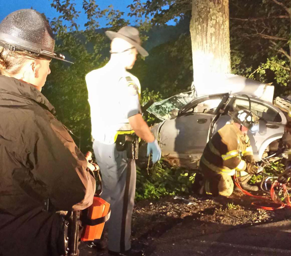 Troopers Diane Vance and G.J. Neagle watch as firefighters use extrication equipment to remove two dead bodies from the car after a crash early Saturday morning in Vassalboro.