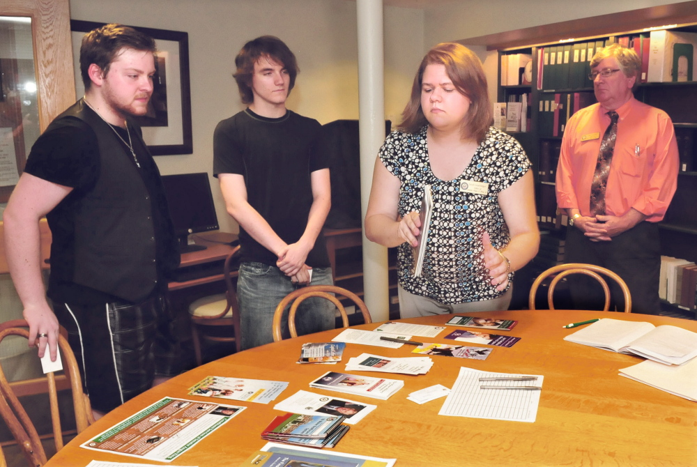 Sarah Graettinger, center right, and Ben Tucker, right, representatives from U.S. Sen. Angus King's office, give pamphlets and information on education to Tristan Huntoon, left, of Madrid, and Nick Pelletier, of Bingham, during an outreach program visit Tuesday at the Farmington Public Library.