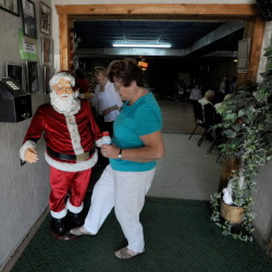Shirley Phillips, a Christmas in July volunteer for the past 22 years, turns on Santa Claus on Thursday for the annual celebration at Melody Ranch in Fairfield.