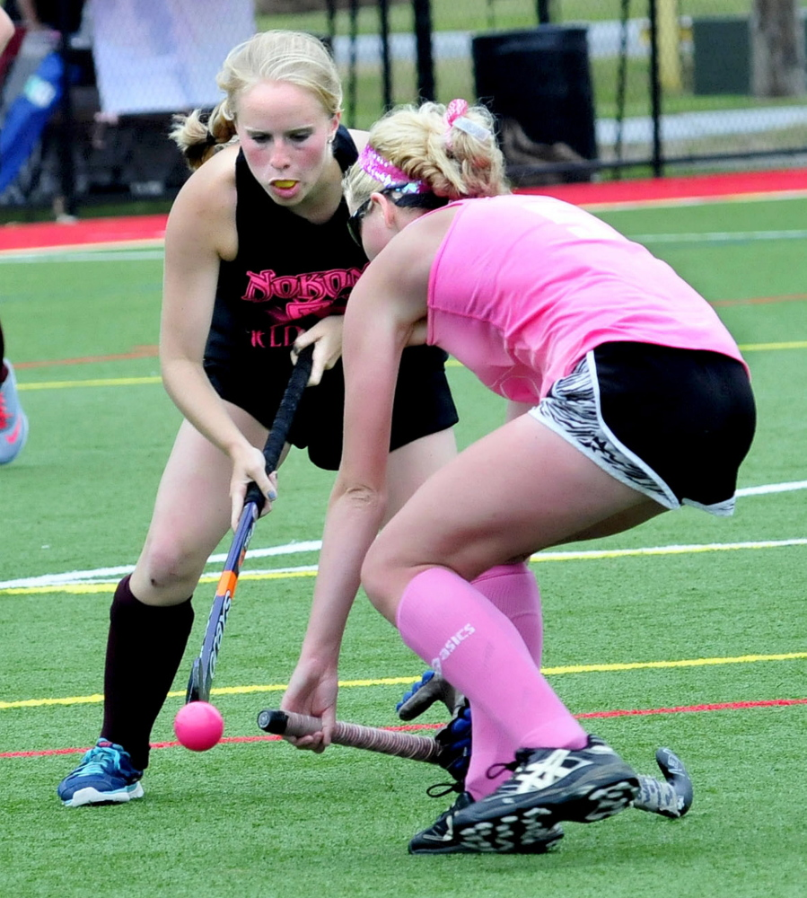 Hannah Merservey, left, of Nokomis and Lauren Leblanc, of Skowhegan, battle for the ball during a field hockey fundraiser event at Thomas College in Waterville on Saturday.