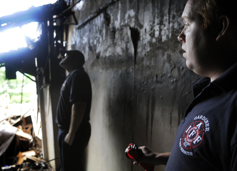Gardiner firefighter Gary Hickey, left, and Fire Department Capt. Nate Sutherberg wait on Sunday in a doorway for colleagues to search the burned-out shell of 235 Water St. for missing equipment. The crew hoped to recover gear lost in the blaze that destroyed the structure last Thursday.