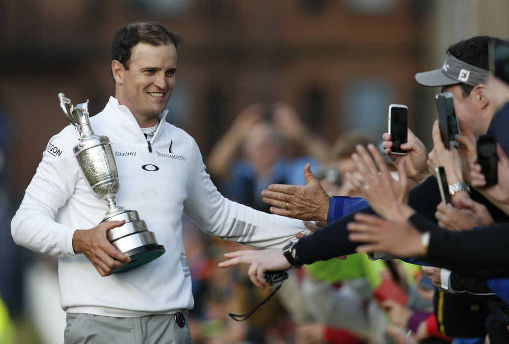AP photo   Zach Johnson celebrates with members of the public as he holds the trophy after winning a playoff after the final round at the British Open on Monday.