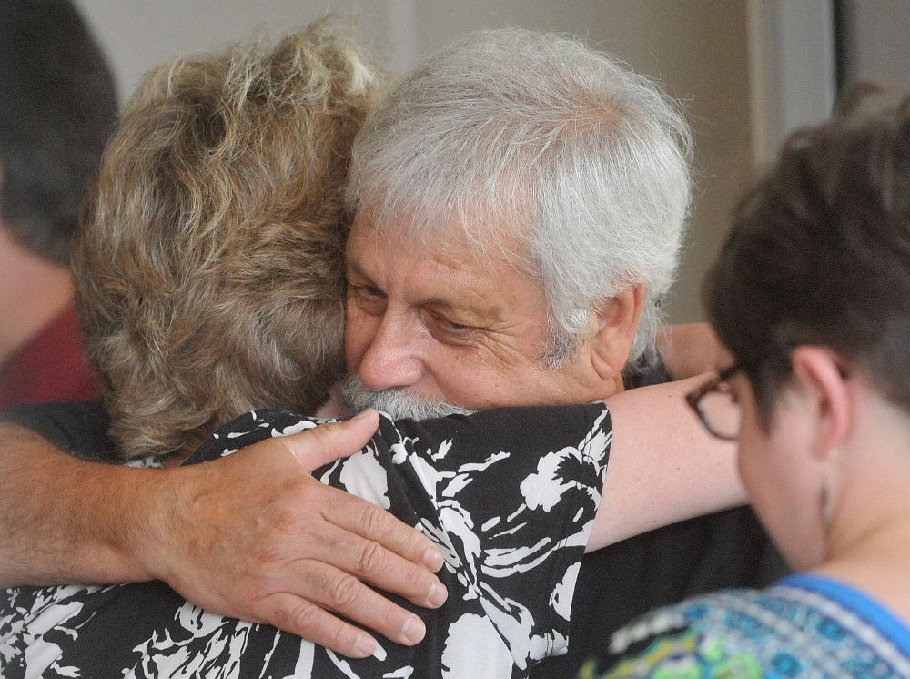 Jared Nightingale, husband of Karen Nightingale, is comforted by friends in July 2014 before his late wife's memorial service at Lawrence High School in Fairfield.