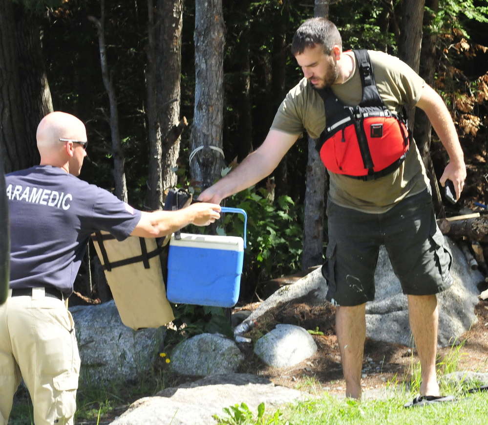 Lake George Regional Park Director Jeff McCabe, right, hands gear to a paramedic as boat operator Llewellyn Ryder was being checked inside an ambulance after he and boat overturned on Lake George in Canaan on Wednesday. McCabe jumped into the water to help Ryder get to shore.