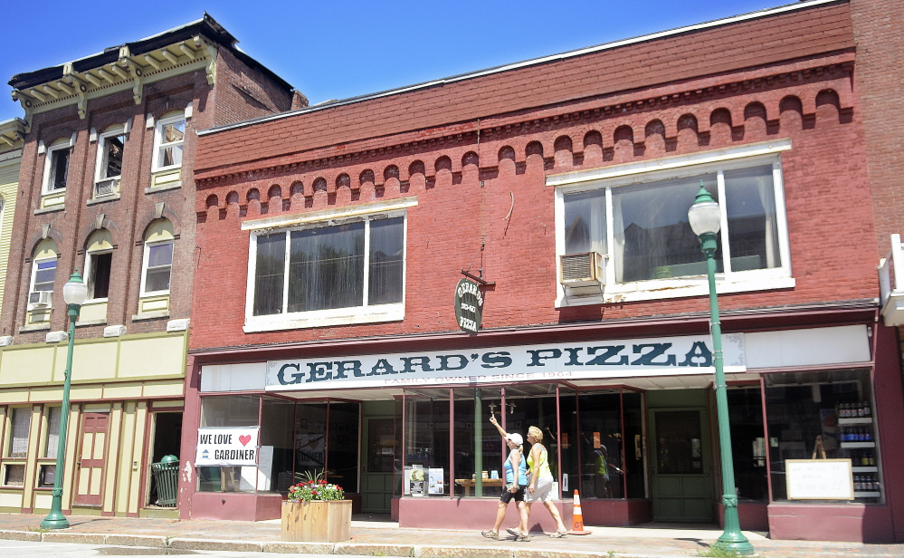 People walk past Gerard's Pizza in Gardiner, which is next door to the building where the fire started.
