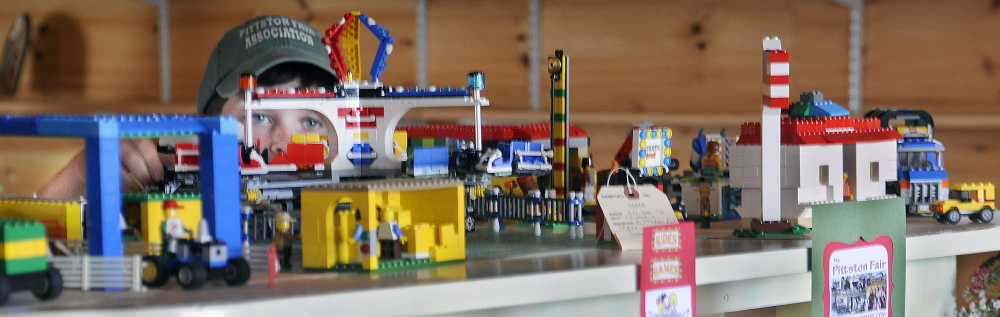 Jared Weeks, 9, tests the Ferris wheel he assembled out of Legos that he displayed in the Exhibition Hall at the Pittston Fair on Wednesday.