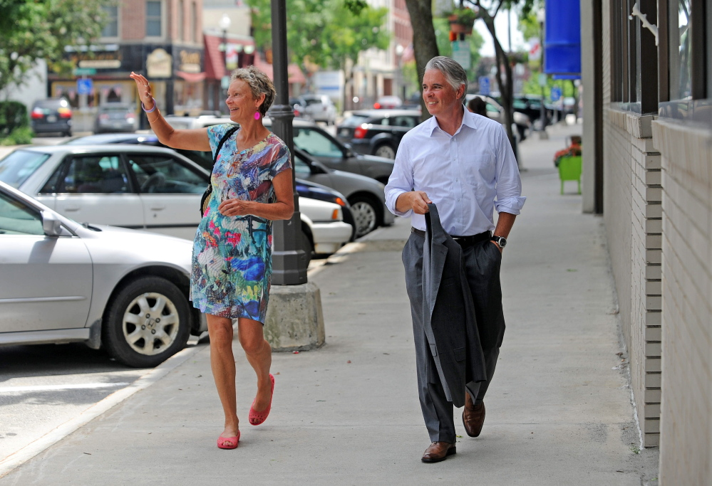 Karen Heck, former mayor of Waterville, walks with Colby College President David Greene on July 1, 2014, on Main Street in downtown Waterville.