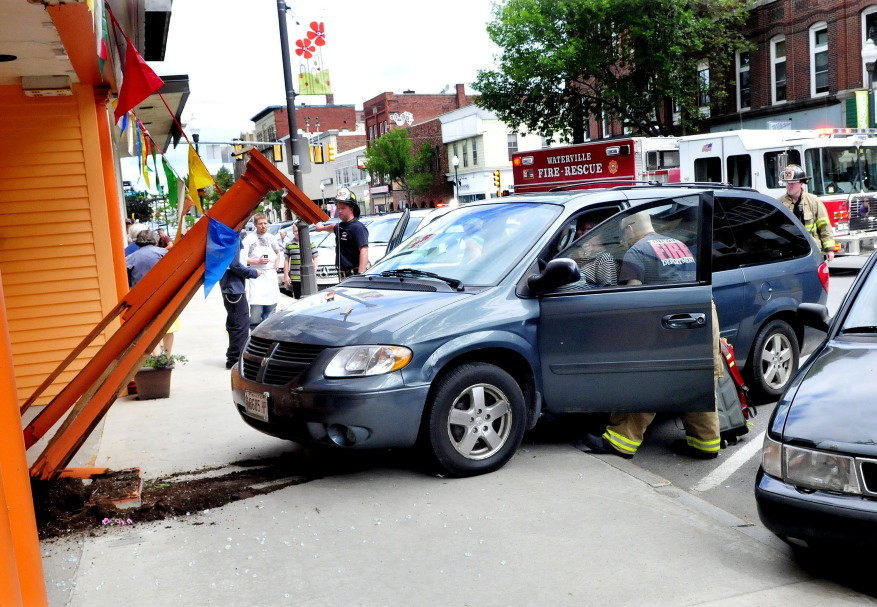 Rescue workers treat Elaine Jacques, the driver of the van that crashed into the front of the Jewel of India Restaurant Thursday morning, smashing a glass entry door and wood structure in front on Main Street in Waterville.
