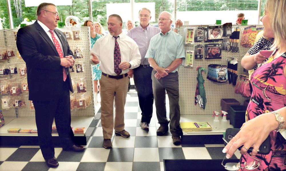 Oakland Pharmacy owner Shane Savage, center, speaks Thursday during a ribbon cutting ceremony for the relocation of his Oakland pharmacy. The event was attended by Gov. Paul LePage, left, his father Bud Savage, right, business partner Clay Smith and Kim Lindloff of the Mid-Maine Chamber of Commerce, among others.