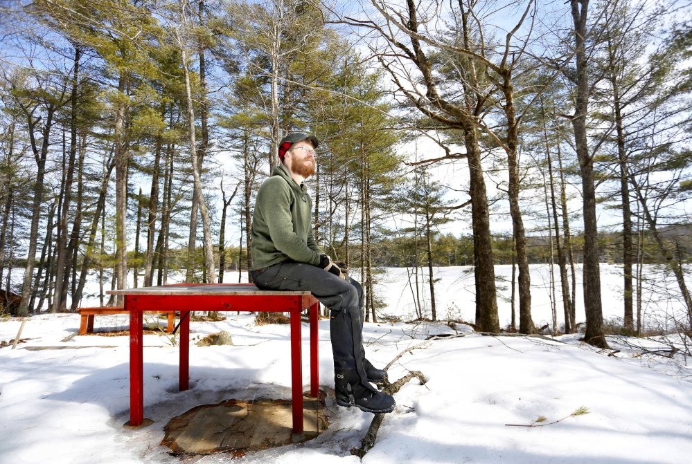 Andy McEvoy, director of Hidden Valley Nature Center, one of the five land conservation organizations proposing to merge, sits at the location for a new lakeside cabin on Little Dyer Pond at the center in Jefferson in this March 2014 file photo.