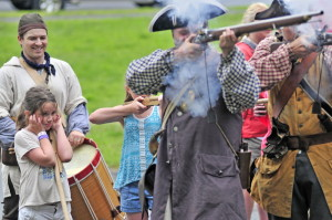 Emily Day, 9, of Auburn, left, covers her ears as re-enactors fire a volley Saturday during an Old Fort Western encampment set up for the annual Old Hallowell Day celebration in Hallowell. Peter Morrissey, as Capt. James Howard, right, led children in marching drills around a field beside Hallowell Seafood.
