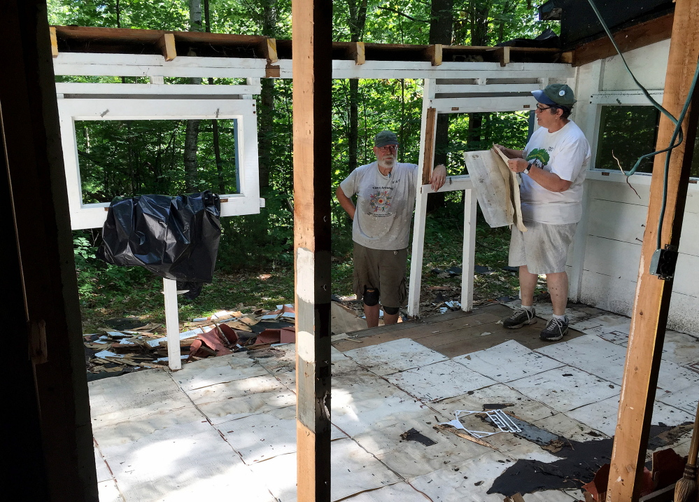 Linda and Bob Webster pull Morning Sentinel printing mats from the floor of their Rockwood Lane camp in Smithfield on Wednesday.