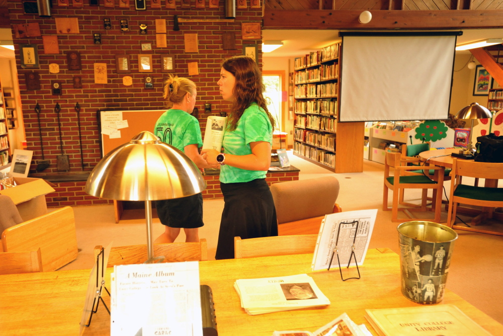 Jlynn Frazier, right, and Erica Hutchinson prepare for the arrivals of alumni and college friends at Clifford Hall for the 50th anniversary of Unity College on Friday.