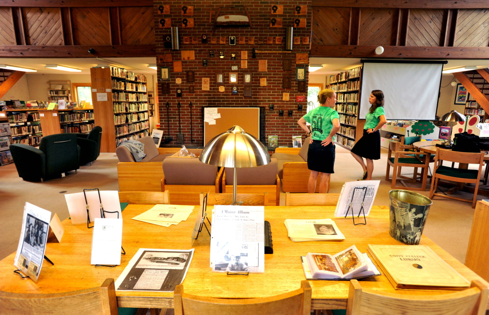 Jlynn Frazier, right, and Erica Hutchinson, center, both development officers at Unity College, prepare the library for the 50th anniversary of Unity College on Friday.