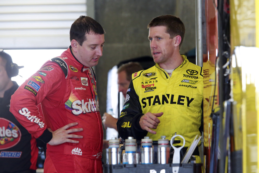 Kyle Busch, left, talks with Carl Edwards during practice Friday for the NASCAR Sprint Cup Brickyard 400 at Indianapolis Motor Speedway in Indianapolis.