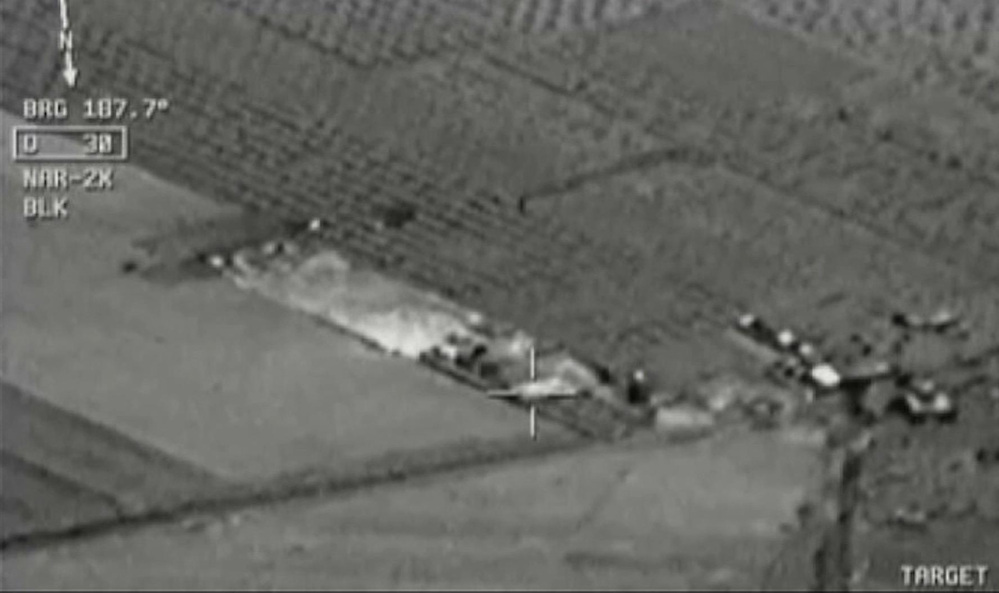 Image from aircraft cockpit video released by Turkey's state-run agency Anadolu Friday, July 24, 2015, of what they report to be Turkish warplanes striking Islamic State group targets across the border in Syria. Black object at centre above target is bomb shortly before impact. Earlier a government official said three F-16 jets took off from Diyarbakir airbase in southeast Turkey early Friday and used smart bombs to hit three IS targets across the Turkish border province from Kilis.