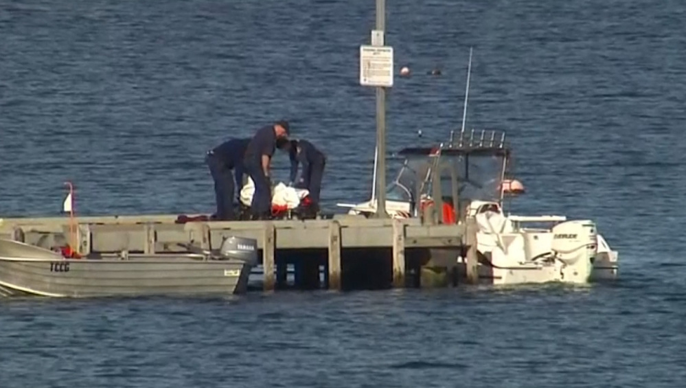 In this image taken from video, police carry a body in a bag and place it in on a stretcher on a jetty in Triabunna, off the Australian island state of Tasmania, on Saturday.