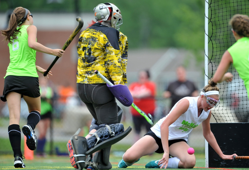 Staff photo by Michael G. Seamans   East players Meg Dowd, left, scores on West goalie Cassidy Smith (31)during the East/West all-star game Saturday at the Maine Field Hockey Festival at Thomas College.