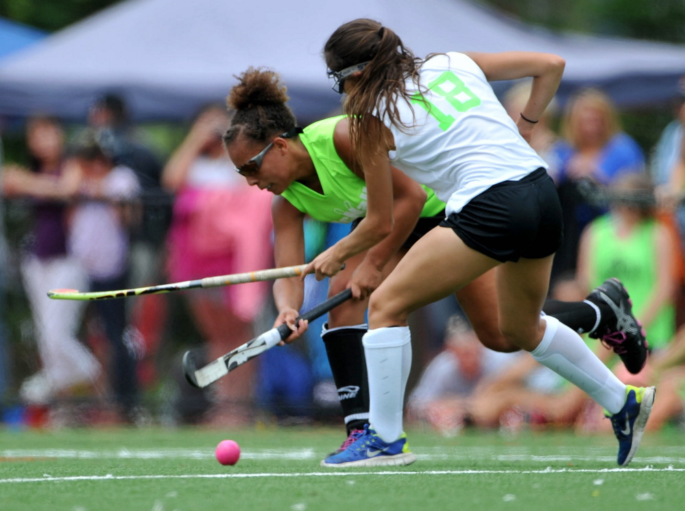 Staff photo by Michael G. Seamans   East player Victoria Newbill, left, battles for the ball with aa West defender during the East/West all-star game Saturday at the seventh annual Maine Field Hockey Festival at Thomas College.